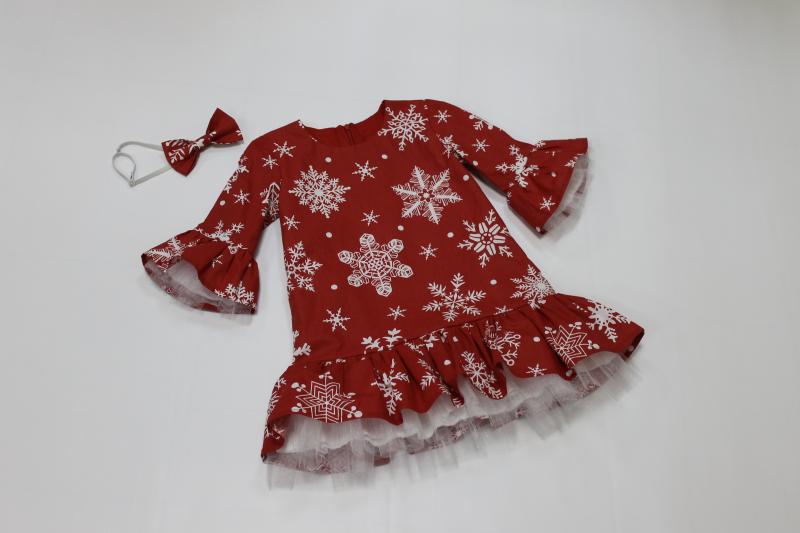 Нарядное платье на девочку  с снежинками на красном фоне